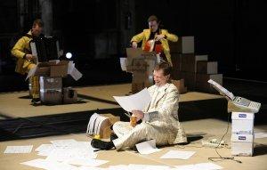 Perttu Haapasen monodraamassa Nothing to Declare arkinen toimistotyo? saa absurdeja ulottuvuuksia. Etualla baritoni Nicholas Isherwood.